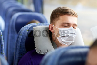 man in mask sleeping in travel bus with pillow