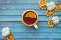 Cotton bolls and cup of hot warming tea with orange on blue wooden table
