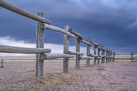 wooden fence and dark stormy sky in prairie