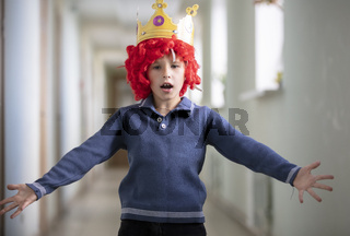 Child in a red wig and a crown. Clown boy