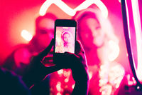 Young woman is photographed in a night club. Focus on male hands making photo by smartphone in foreground. Abstract blurred background with neon lights