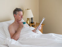Single caucasian senior man in inclined bed and reading from magazine