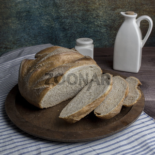 Fresh round bread with slices on a wooden tray. Rustic still life bread salt butter, tableware flax linen tablecloth