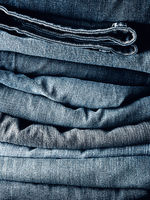Stacked blue jeans using as background