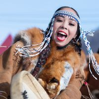 Woman in national clothing indigenous inhabitants Kamchatka dancing with tambourine. Concert, celebration Koryak national holiday Day of Seal Hololo