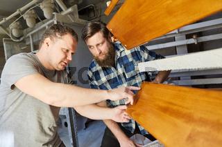 Zwei Schreiner besprechen die Holzarbeiten