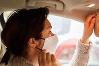 Frau mit Mundschutz überprüft ihre Maske in Auto