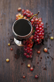 Glass of wine and grape on wooden background