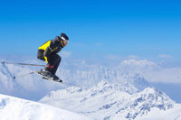 Jumping skier at mountains