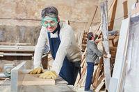 Schreiner hobelt Holz in Schreinerei