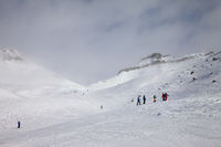 Skiers and snowboarders descent on snowy ski slope and overcast misty sky