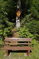 Wegkreuz und Sitzbank im Wald