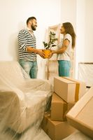 Moving in, happy male and female unpacking boxes, holding plant