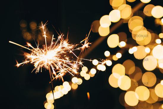 Sparklers on blurred christmas lights. Festive mood