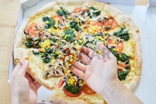 Hand hält ein Pizzastück einer Gemüse Pizza
