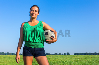 Standing young woman holds football outside