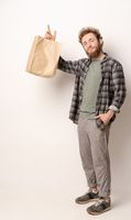Man in plaid shirt holding brown paper bag isolated on white background. Delivery concept. Paper bag for takeaway food. Courier with a bag on white background
