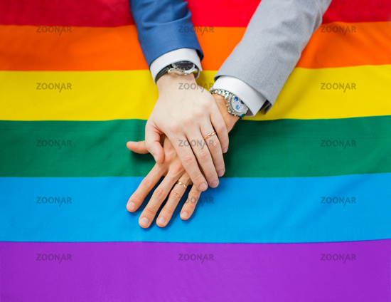 close up of male gay couple hands on rainbow flag