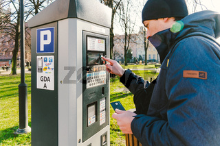 Payment for parking in the City of Gdansk, Poland on February 8, 2020. A person uses monobank credit card for nfc payment in parking terminal. Paid Automatic payment for parking places in city