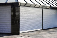 closed business shop or store front with roller shutters