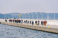 A crowd of people walks on a wooden pier in Sopot, Poland on July 20, 2020 on a sunny winter day near the Baltic Sea. Ative winter vacation near the sea. Hiking and a walk in Sopot