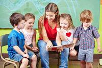 Kinder mit Erzieher lesen Buch im Kindergarten