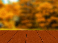 Empty wooden table with blurred autumn forest.