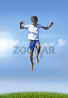 A boy jumps on a summer background of blue sky
