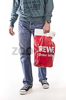 Mann mit einer Plastiktüte von Rewe