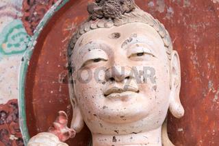 smiling buddha closeup in maiji mountain grottoes
