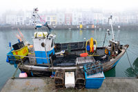 A small industrial fishing boat moored in Weymouth being loaded with fishing pots.