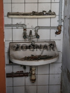 verdrecktes Waschbecken mit Wasseranschluss