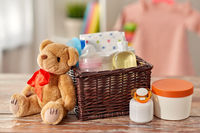 baby things in basket and teddy bear toy on table