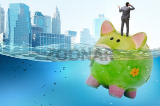 Businessman in debt concept with piggybank