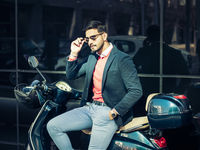 Trendy man sitting on scooter in city setting
