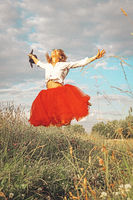Beautiful young woman jumping on a green meadow with a colored red dress. Happiness and joyful freedom people concept. Beautiful young woman in a field with daisies.