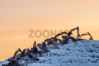 Silhouettes of many excavators working on a huge mountain in a garbage dump