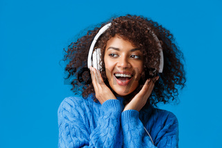 Close-up portrait cheeky and carefree happy smiling african-american modern gen-z girl with afro haircut, curly hair, listen music in headphones smiling delighted, enjoy new earphones
