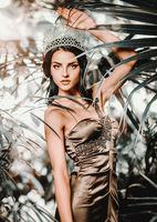 Gorgeous young 20s woman wearing long evening elegant dress and tiara on head posing surrounded by lush tropical foliage trees. Beauty and fashion concept