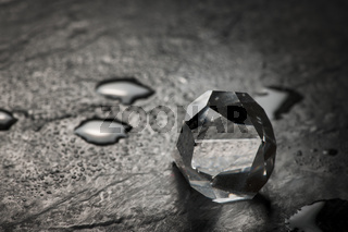 Cut crystal on slate with drops
