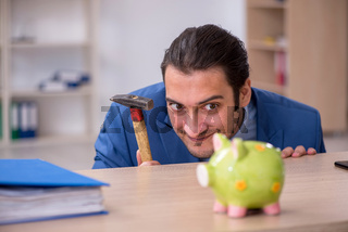 Aggressive male employee with hammer in budget planning concept