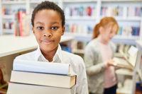 Schüler in Grundschüle trägt Bücher aus Bibliothek