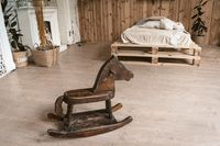 Bedroom in the interior of wood with a wooden horse. There's a children's horse in the foreground. In the background is a bed and a fireplace. High quality photo