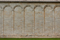 Ancient brick stone wall of Cathedral and tower with columns and bas-reliefs of historical figures. Cathedral of santa maria assunta. May, 2013. Pisa, Italy