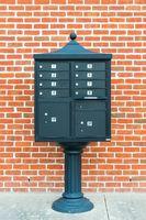 Metal mailbox against brick wall