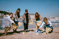 Group of activists friends collecting plastic waste on the beach. Environmental conservation.