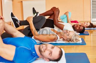 Alte Frau macht Gymnastik im Kurs