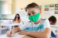 Portrait of boy wearing face mask sitting in class at school