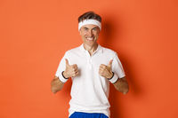 Concept of sport, fitness and lifestyle. Portrait of confident, attractive middle-aged male athlete in workout uniform, showing thumbs-up in approval and smiling, orange background