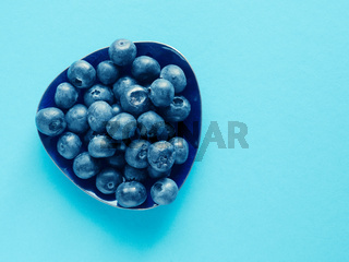 Tasty organic blueberries on a blue paper background